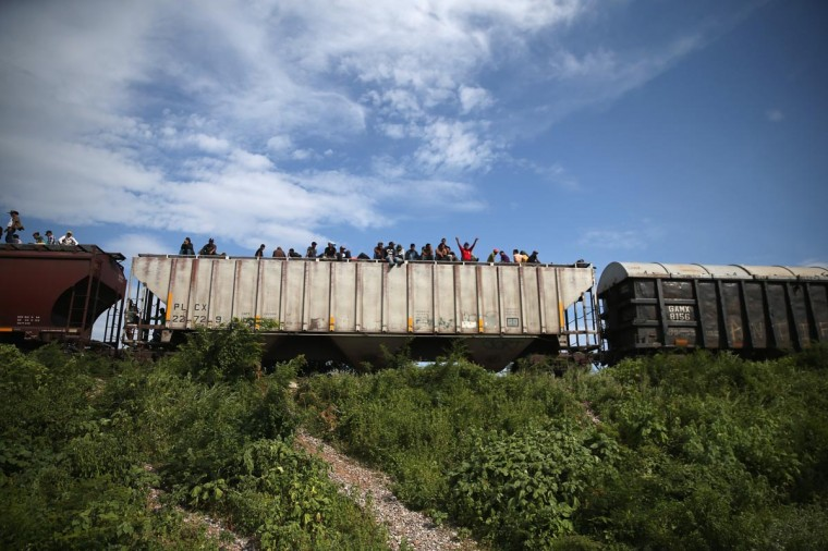 Immigrants arrive for a rest stop after a 15 hour ride atop a freight train headed north early on August 4, 2013 in Ixtepec, Mexico. (John Moore/Getty Images)