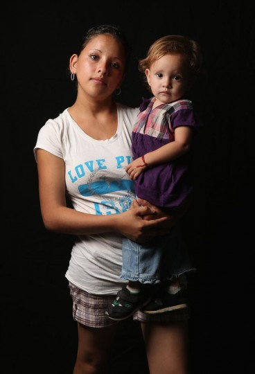 Salvadorian immigrant Stefanie Elizabeth, 17, holds her daughter Emily Nicole, 18 months, while spending another night at the Hermanos en el Camino immigrant shelter on August 5, 2013 in Ixtepec, Mexico. They, along with Emily Nicole's father Hector Manuel, 30, have been staying at the shelter for two months while awaiting Mexican immigration documents to allow them to safely travel to the U.S. border by bus, where they will try to illegally cross into the United States. (John Moore/Getty Images)