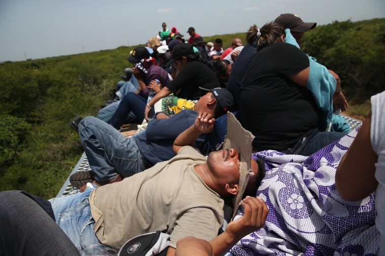Central American immigrants ride north on top of a freight train on August 6, 2013 near Juchitlan, Mexico. (John Moore/Getty Images)