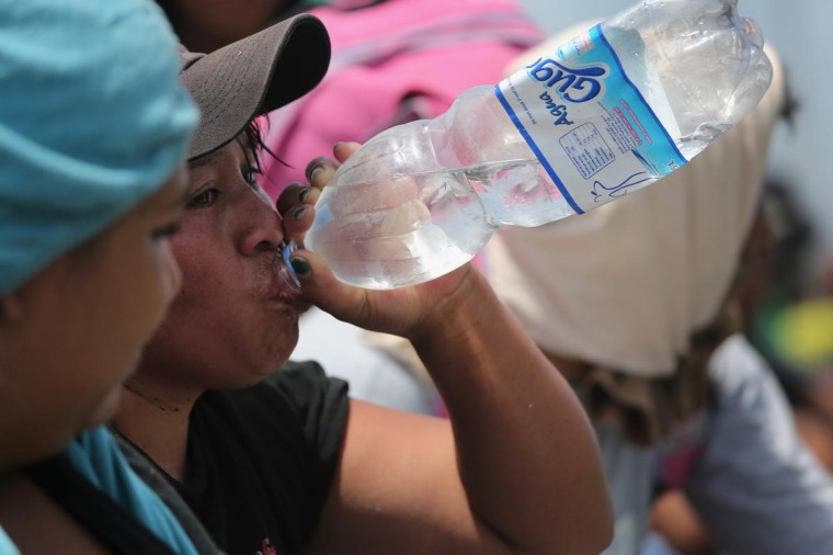 Central American immigrants try to stay hydrated while riding on top of a freight train on August 6, 2013 in Ixtepec, Mexico. (John Moore/Getty Images)