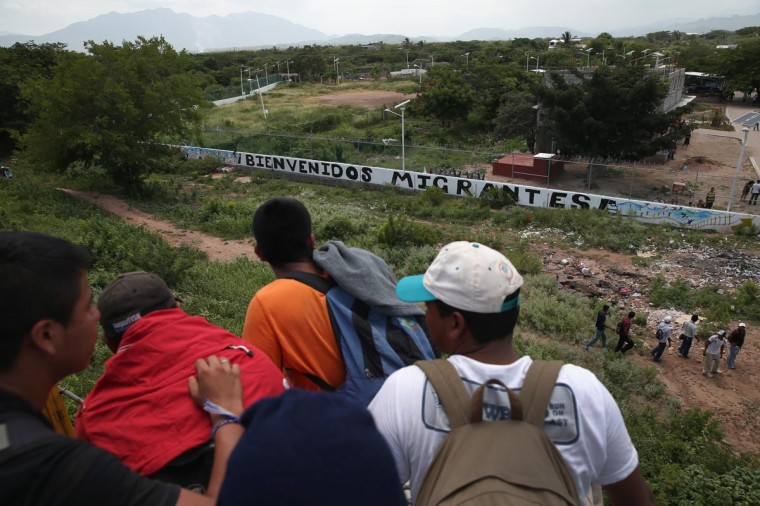 """Central American immigrants arrive on top of a freight train to the Hermanos en el Camino immigrant shelter on August 6, 2013 in Ixtepec, Mexico. The sign outside reads """"Welcome Migrants."""" (John Moore/Getty Images)"""