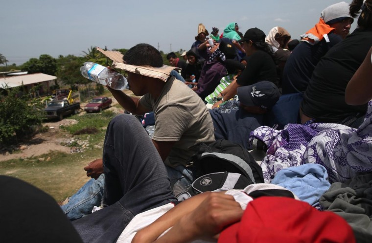Central American immigrants ride under a blazing sun on top of a freight train on August 6, 2013 near Juchitlan, Mexico. (John Moore/Getty Images)