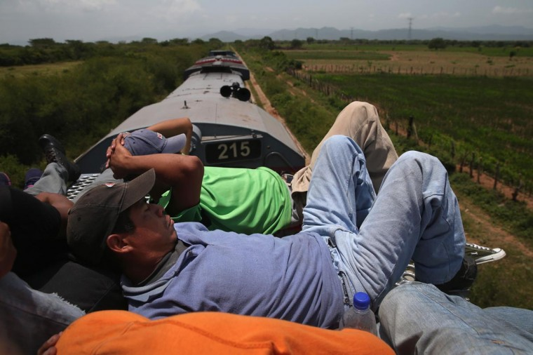 Central American immigrants fall asleep on top of a freight train on August 6, 2013 near Juchitlan, Mexico. (John Moore/Getty Images)
