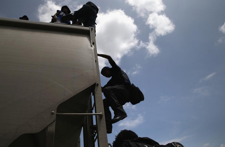 Central American immigrants arrive on top of a freight train for a stop on August 6, 2013 in Ixtepec, Mexico. (John Moore/Getty Images)