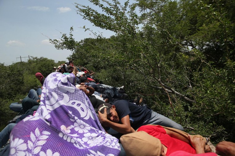 Central American immigrants duck tree branches while riding on top of a freight train on August 6, 2013 near Juchitlan, Mexico. (John Moore/Getty Images)