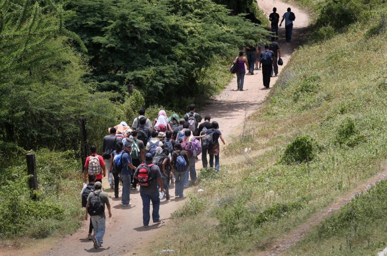 Central American immigrants walk after arriving on a freight train for a stop on August 6, 2013 in Ixtepec, Mexico. Thousands of Central American migrants ride the trains, known as 'la bestia', or the beast, during their long and perilous journey north through Mexico. (John Moore/Getty Images)