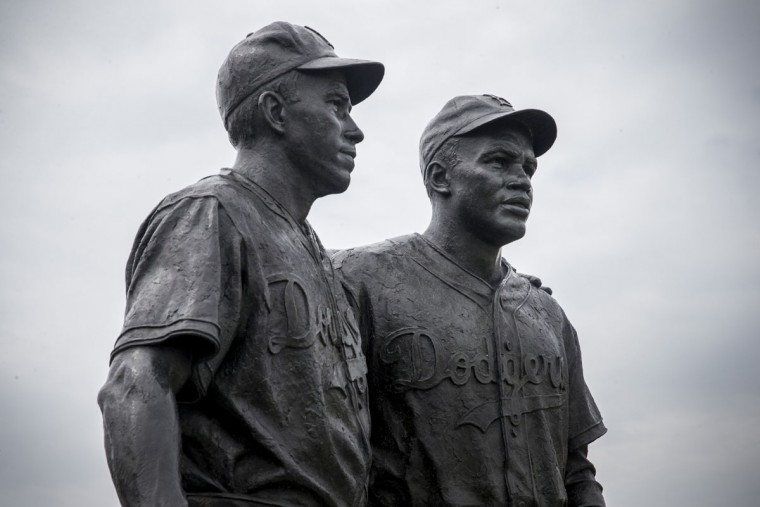 A statue of Pee Wee Reese (left) and Jackie Robinson stands after being cleaned of racist graffiti on August 9, 2013 in the Coney Island neighborhood of the Brooklyn borough of New York City. Robinson broke the color barrier for Major League Baseball in 1947 when he joined the Brooklyn Dodgers and Reese was a teammate and supporter. The statue, which was unveiled in 2005, was recently defaced with racist graffiti and the city recently finished restoring the statue using sandblasting and power-washing. (Andrew Burton/Getty Images)