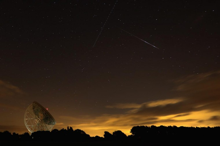 A Perseid meteor streaks across the sky over the Lovell Radio Telescope at Jodrell Bank on August 13, 2013 in Holmes Chapel, United Kingdom.The annual display, known as the Perseid shower because the meteors appear to radiate from the constellation Perseus in the northeastern sky, is a result of Earth's orbit passing through debris from the comet Swift-Tuttle. (Christopher Furlong/Getty Images)