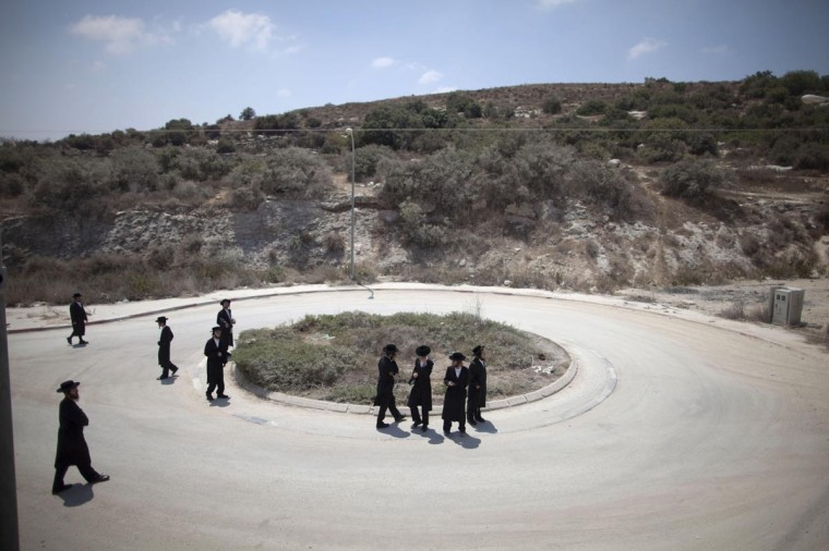 Ultra-Orthodox Jewish men walk during a demonstration on August 13, 2013 in Beit Shemesh, Israel. Around a hundred Jews protested against the construction of a new housing unit on the site which they belive will be located on ancient Jewish graves. (Lior Mizrahi/Getty Images)