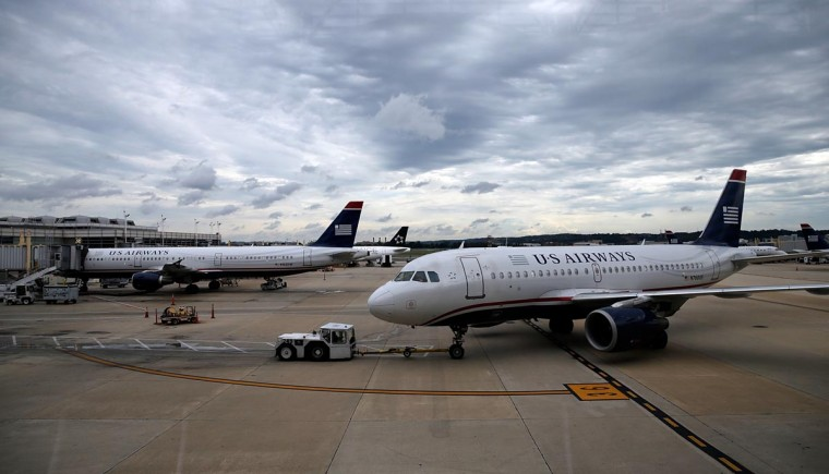A US Airways jet taxies at Ronald Reagan Washington National Airport August 13, 2013 in Arlington, Virginia. The U.S. Justice Department, and attorneys general from six states, filed legal actions today attempting to prevent the planned merger of US Airways and American Airlines as a violation of antitrust law. (Win McNamee/Getty Images)