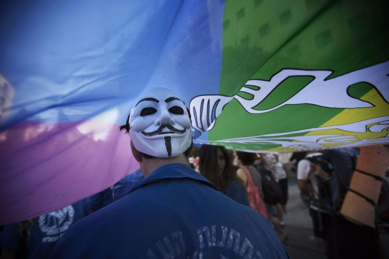 """An Israeli wears a mask under a giant flag during the annual gay pride parade on August 1, 2013 in Jerusalem. 2,500 people took part in the gay pride parade calling for equal rights, as 150 Ultra Orthodox Jews demonstrated to denounce the """"abomination"""" of homosexuality. (Menahem Kahana/AFP/Getty Images)"""
