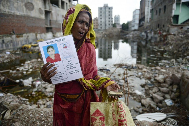 A mourner holds up a portrait of her missing relative, presumed dead following the April 24 Rana Plaza garment building collapse, and a bone fragment believed to be from one of the many unidentified remains of killed garment workers, at the scene on the one hundredth-day anniversary of the disaster in Savar, on the outskirts of Dhaka, on August 2, 2013. Hundreds of garment workers staged demonstrations at the site of Bangladesh's worst industrial disaster, demanding compensation for the survivors and a full account of the missing laborers of the April 24, 2013 factory building collapse that killed 1,129 people. (Munir uz Zaman/AFP/Getty Images)