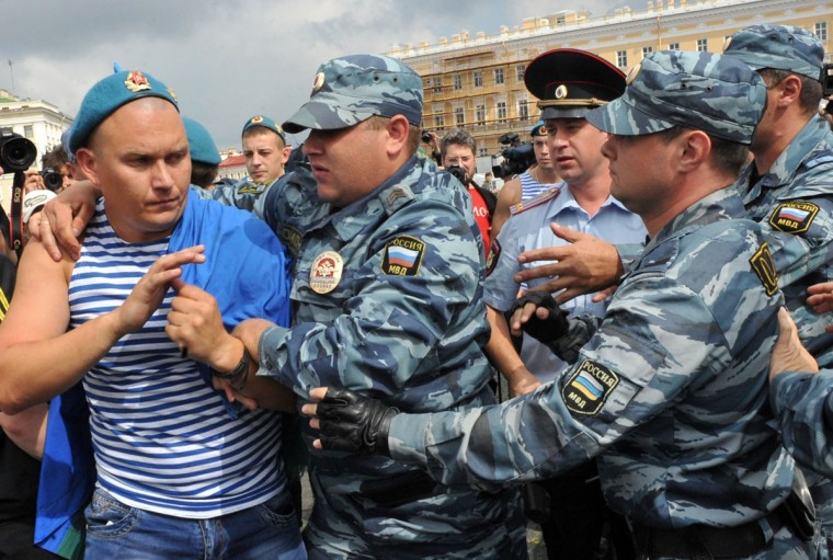 Russian riot police detain a paratrooper veteran (left) on August 2, 2013 in St. Petersburg. Russian paratroopers scuffled with LGBT rights activist Kirill Kalugin, who stood protesting against gay rights violations during the celebration. (Olga Maltseva/AFP/Getty Images)