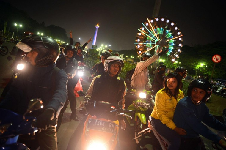 "In this photograph taken August 3, 2013, Indonesians ride motorcycles in a festive motorcade called ""sahur on the road"" around central Jakarta. As the Islamic holy month of Ramadan enters its final week before the Eid al-Fitr celebrations, residents hold a weekend dawn vigil in motorcades taking packed meals to distribute to street beggars, then conclude their ride with a pilgrimage to a mosque to perform dawn prayers. (Romero Gacad/AFP/Getty Images)"