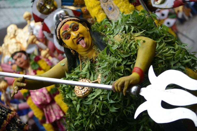 An Indian artist dressed as Hindu Goddess MahaKali performs while in a trance during the final procession of the eleven-day traditional festival of 'Bonalu', a ritual offering to the goddess MahaKali, at Sri Akkanna Madanna Mahankali Temple in Hyderabad on August 5, 2013. The Goddess is honoured mostly by women during Bonalu festival with offerings of food and dancing. (Noah Seelam/AFP)