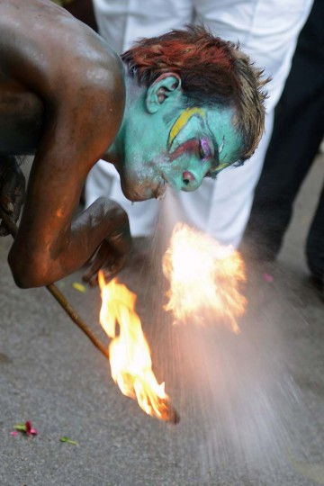 A fire breather performs during the final procession of the eleven-day traditional festival of 'Bonalu', a ritual offering to the goddess MahaKali, at Sri Akkanna Madanna Mahankali Temple in Hyderabad on August 5, 2013. The Goddess is honoured mostly by women during Bonalu festival with offerings of food and dancing. (Noah Seelam/AFP)