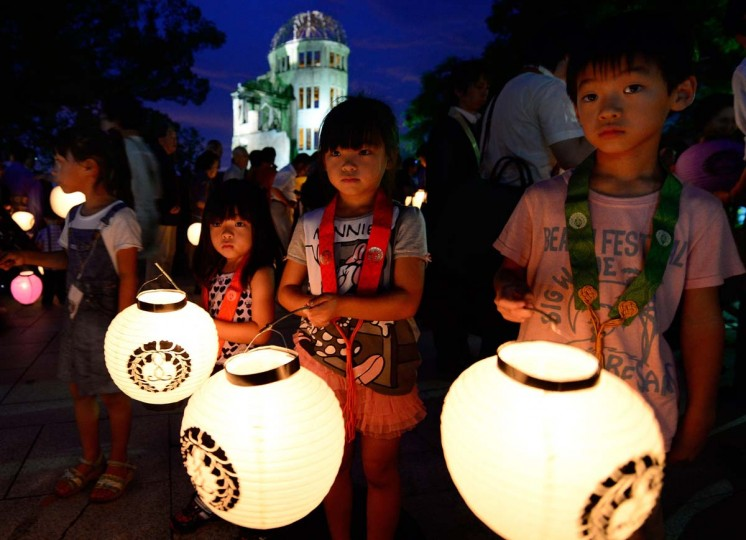 Children carry lanterns to pray for atomic bombing victims in front of the Atomic Bomb Dome at the Peace Memorial Park in Hiroshima on August 5, 2013. Tens of thousands of people were expected to gather at a peace memorial park in Hiroshima on August 6 to mark the 68th anniversary of the US atomic bombing of the Japanese city. (Toru Yamanaka/AFP)