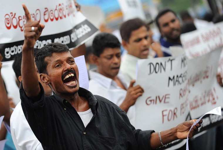 A supporter of Sri Lanka's Marxist JVP or People's Liberation Front demonstrates in the capital Colombo on August 5, 2013 to denounce a deadly army crackdown on villagers who were demonstrated against contaminated water supplies. At least three people were killed and another 50 wounded in an army shooting on protesters at a village just outside the capital August 1, 2013 sparking wide-spread condemnation of the government action. (Ishara S. Kodikar/AFP)
