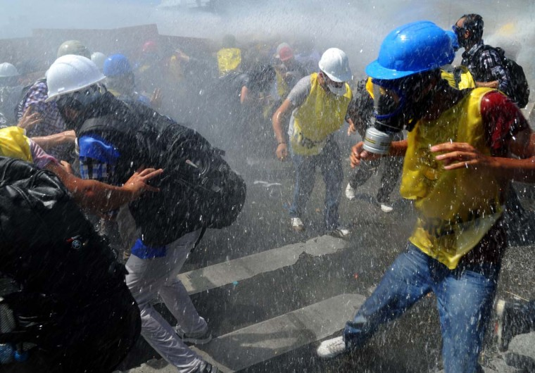 Police disperse demonstrators with water cannon during clashes near a courthouse in Silivri, near Istanbul, on August 5, 2013, after a court decision to sentence a former army chief and other top brass to life in prison in a high-profile trial of 275 people accused of plotting to overthrow the Islamic-rooted government. Ex-military chief Ilker Basbug, along with several other army officers, were sentenced to life in prison, while 21 people were acquitted, according to the verdicts issued so far. The trial has been seen as as a key test in Prime Minister Recep Tayyip Erdogan's showdown with secularist and military opponents during his decade-long rule. (Bulent Kilic/AFP)