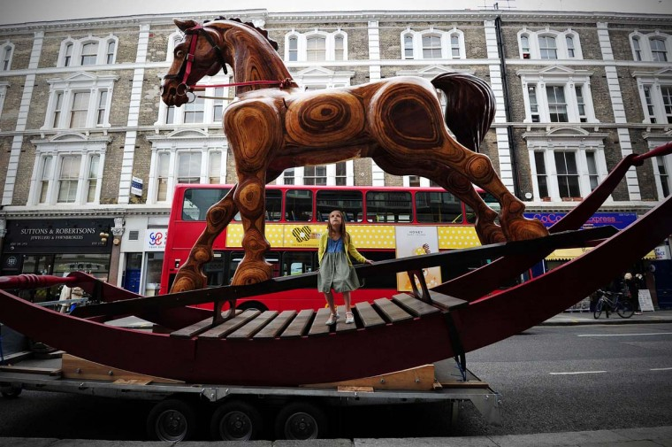 Riva Lemanski, 6, poses for photographers next to a giant rocking horse known as 'Bigger Bertie' in central London on August 5, 2013. Thought to be the biggest hand-carved rocking horse in the world, it has a trap door in the belly and another in the saddle. Originally made for the World Skills Show 2011, the horse forms part of the 'Out of the Ordinary' sale at Christies showroom on September 5, 2013 and is expected to fetch GBP 25,000 - 40,000 ( USD 38,344 - 61,351 Euros 28,950 - 46,322) . (Carl Court/AFP)