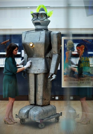 A member of staff poses with a robot called 'Cygan' at Christies auction house in central London on August 5, 2013. Made in 1957, it was one of the most sophisticated robots of its time with an ability to accept spoken commands and respond to light rays. Forming part of the 'Out of the Ordinary' sale on September 5, 2013 it is expected to fetch between GBP 8,000 - 12,000 ( USD 12,259 - 18,389, Euros 9,261 - 13,890GBP. (Carl Court/AFP)