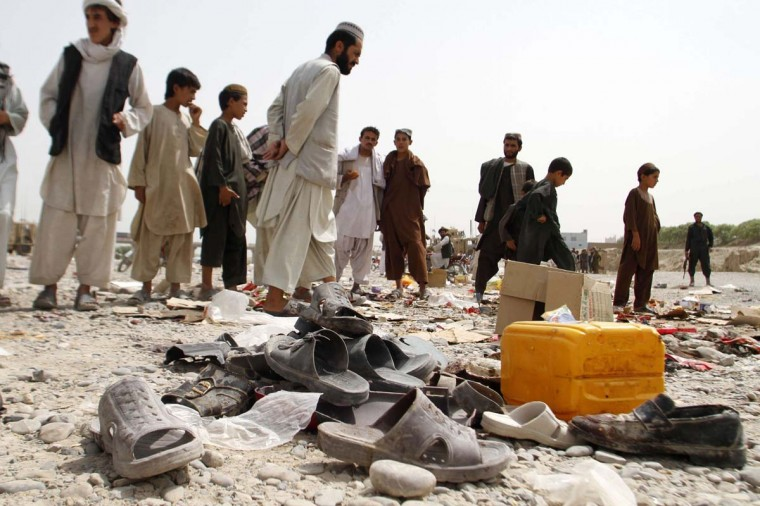 Afghan men walk amidst sandals, mostly from victims of a bomb blast, strewn at the roadside on the outskirts of Kandahar on August 5, 2013. An improvised bomb went off in a weekly bazaar outside Kandahar city, killing four civilians and wounding 22 others. The bombing happened in a flea bazaar that opens every Monday on the outskirts of Kandahar city. (Jangir/AFP)