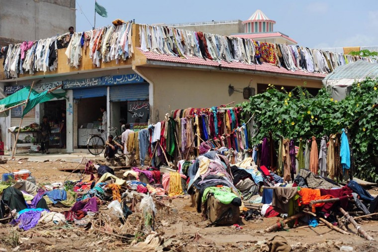 Residents look on as clothes are hung out to dry in the aftermath of floods in Karachi on August 5, 2013. Pakistani disaster relief officials issued fresh flood warnings after the death toll from heavy monsoon rains rose to 45 and waters paralyzed parts of the largest city Karachi. (Rizwan Tabassum/AFP/Getty Images)