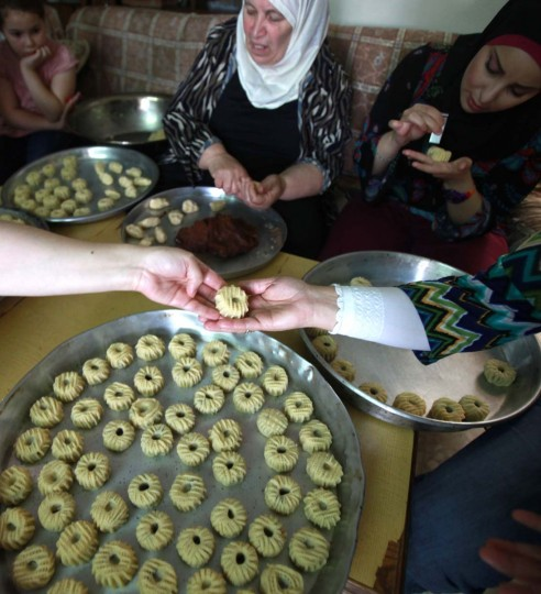 A Palestinian family prepare traditional biscuits popular on the occasion of Eid al-Fitr at their house in the West Bank city of Ramallah, on August 5, 2013. Muslims around the world are preparing to celebrate the Eid al-Fitr holiday, which marks the end of the fasting month of Ramadan. Preparations include buying new clothes, toys and special sweets. (Abbas Momani/AFP)