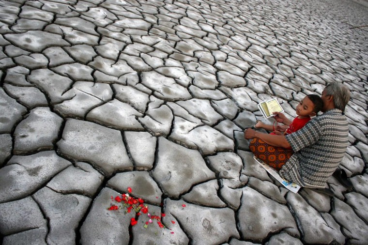 In this photograph taken on August 7, 2013, an Indonesian man with his son pray after offering flowers on dried volcanic mud for family members who died during a volcano eruption in Sidoarjo in eastern Java island. Some Indonesians mark Eid al-Fitr with pilgrimages to cemeteries to remember their dead. The May 2006 disaster killed 12 people, displaced nearly 50,000 and buried 13 villages. (M. Andika/AFP/Getty Images)
