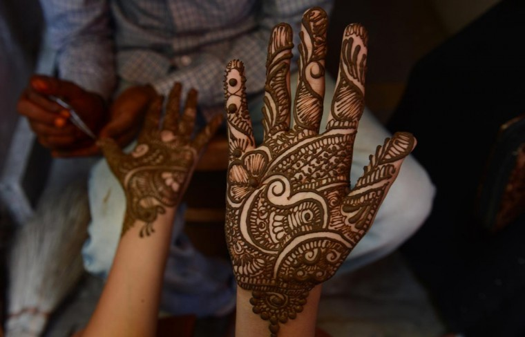 A young Kashmiri woman admires her hand after it was decorated with henna at a market ahead of the Muslim festival of Eid al-Fitr in Srinagar on August 8, 2013. (Tauseef Mustafa/AFP/Getty Images)