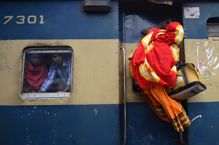 A Bangladeshi passenger (R) climbs on top of a train as other passengers (R) look on from a compartment window as they rush home to their respective villages to be with their families ahead of the Muslim festival of Eid al-Fitr, in Dhaka on August 8, 2013. (Munir uz Zaman/AFP/Getty Images)