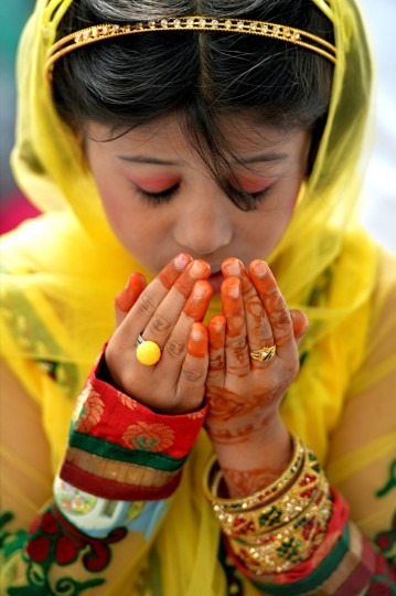 A young Indian Muslim offers Eid al-Fitr prayers at the Idgah Maidan in Bangalore on August 9, 2013. Muslims around the world are celebrating Eid al-Fitr, which marks the end of the fasting month of Ramadan. (Manjunath Kiran/AFP/Getty Images)