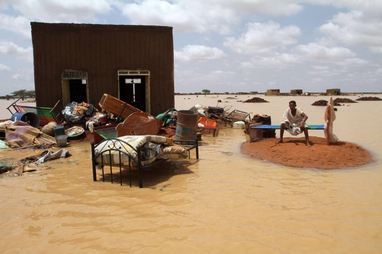 A Sudanese man sits next to his house in a flooded street on the outskirts of the capital Khartoum on August 10, 2013. Drainage is poor in the capital, where even a little rain can cause flooding but this year's water surge was unusually severe. (Ashraf Shazly/AFP/Getty Images)