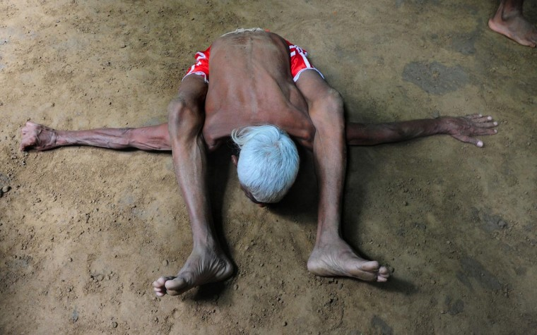 Elderly Indian wrestler Ram Gopal performs during a bout of traditional wrestling organized at the historical Loknath Vyayamsala (Fitness Center) on the occasion of Nag Panchami, in Allahabad on August 11, 2013. This Hindu festival is observed during the monsoon season with prayers and tributes to snakes. (Sanjay Kanojia/AFP/Getty Images)