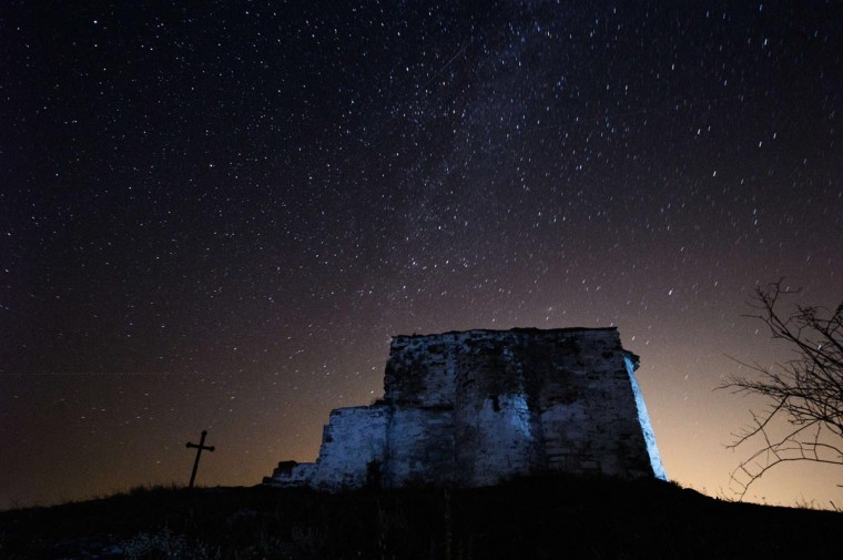 A long exposure image showing a Perseids meteor (L) streaking across the night sky over St. Ioan medieval church near the village of Potsurnentsi, late on August 12, 2013. The Perseid meteor shower occurs every year in August when the Earth passes through the debris and dust of the Swift-Tuttle comet. (Dimitar Dilkoff/AFP/Getty Images)