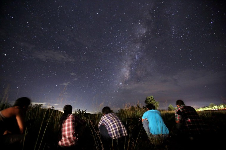 This long-exposure photograph taken on August 12, 2013 shows people watching for the Perseid meteor shower in the night sky near Yangon. The meteor shower occurs every year in August when the Earth passes through the debris and dust of the Swift-Tuttle comet. (Ye Aung Thu/AFP/Getty Images)
