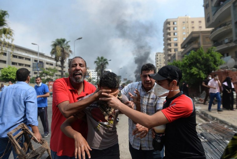 Supporters of Egypt's ousted president Mohamed Morsi and members of the Muslim Brotherhood run from tear gas smoke shot by police to disperse a pro-Morsi camp, on August 14, 2013 in Cairo. (Khaled Desouki/AFP/Getty Images)