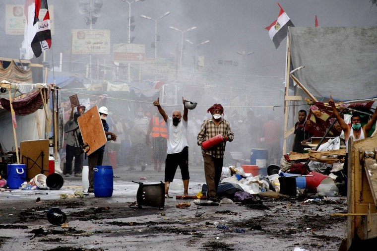 Supporters of ousted president Mohamed Morsi and members of the Muslim Brotherhood gesture as Egyptian security forces (unseen) move in to disperse their protest camp, on August 14, 2013 near Cairo's Rabaa al-Adawiya mosque. (AFP/Getty Images)