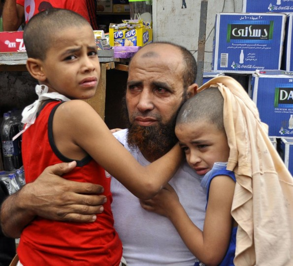 A supporter of Egypt's ousted president Mohamed Morsi holds his children tight as Egyptian security forces move in to disperse by force pro-Islamist protesters in a huge camp in Cairo's Al-Nahda square on August 14, 2013. (Engy Imad/AFP/Getty Images)