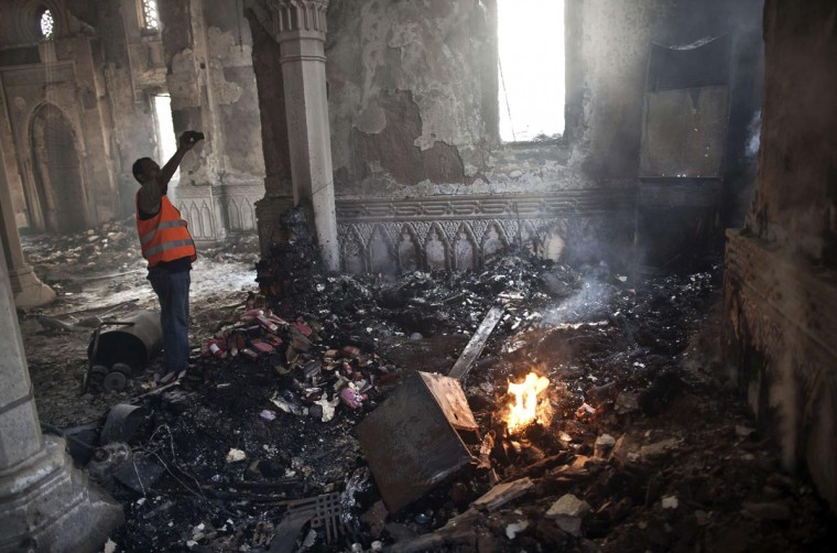 An Egyptian man stands near a burning fire as he takes a picture of the damage at Rabaa al-Adawiya mosque in Cairo on August 15, 2013, following a crackdown on the protest camps of supporters of Egypt's ousted Islamist leader Mohamed Morsi the previous day. The day's violence was Egypt's worst in decades, exceeding even that seen during the 18-day uprising that ousted president Hosni Mubarak. (Mahmoud Khaled/AFP/Getty Images)