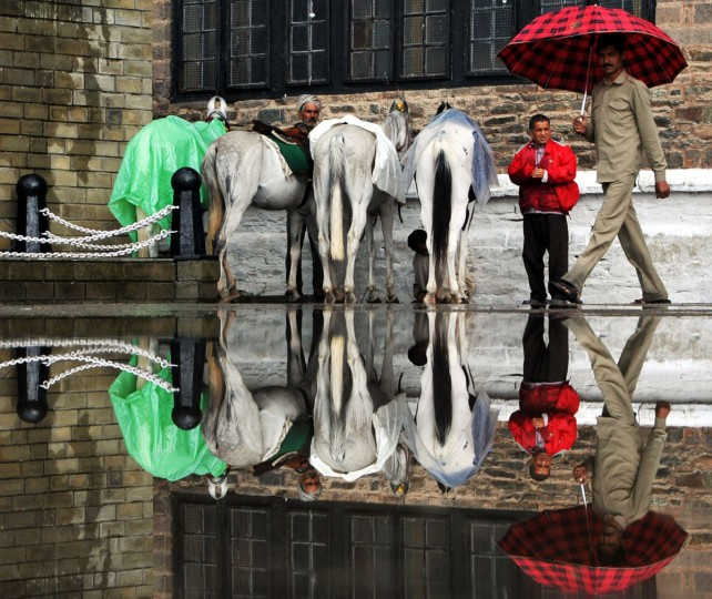 The reflection of horses, their keepers, and an umbrella-toting pedestrian is seen in a puddle of water following heavy monsoon rains in the northern hill town of Shimla on August 16, 2013. The monsoon, which covers the subcontinent from June to September and usually brings flooding, accounts for about 80 percent of India's annual rainfall. (STR/AFP/Getty Images)
