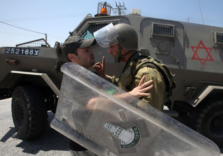 An Israeli soldier wags his finger at a Palestinian protester during the evacuation of Palestinian protesters who were trying to close the main road leading to the Israeli settlement of Efrat in the West Bank city of Bethlehem on August 16, 2013. (Hazem Bader/AFP/Getty Images)