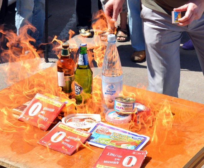Members of a Ukrainian non-governmental organization (NGO) burn goods produced in Russia during a protest in front of the Russia Embassy in Kiev on August 16, 2013. Ukraine is experiencing difficulties with its exports to Russia, the prime minister Mykola Azarov acknowledged on Thursday, amid growing tensions with Moscow over a Kremlin-led Customs Union. (Genya Savilov/AFP/Getty Images)