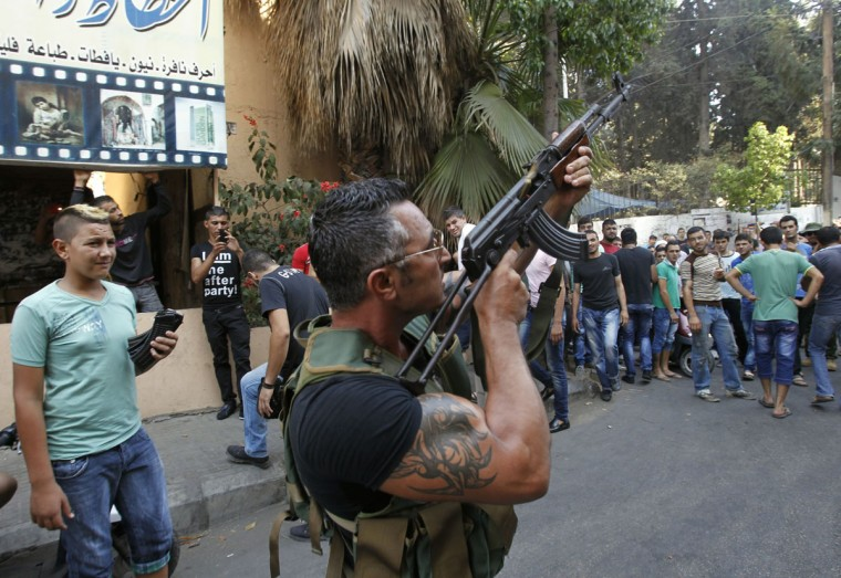 A Lebanese gunman is seen during the funeral procession of Hamad al-Moqdad, one of the Lebanese victims of a car bomb attack that killed dozens in a Beirut stronghold of Shiite group Hezbollah, which backs Syria's embattled president, in the capital on August 16, 2013. Lebanon was holding a day of mourning after the attack. (Anwar Amro/AFP/Getty Images)