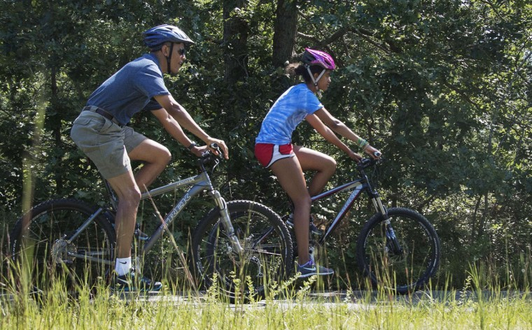 U.S. President Barack Obama (left) rides with his daughter Malia through the Manuel F. Correllus State Forest in West Tisbury, Massachusetts, August 16, 2013, during their family vacation to Martha's Vineyard. (Jim Watson/AFP/Getty Images)