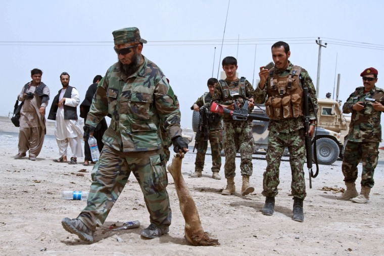 "An Afghan security official drags the severed leg of a suicide attacker at the site of a suicide attack in Kandahar on August 16, 2013. Some fifteen people were injured in the attack on the highway near Kandahar Airport. General Abdul Hameed, Afghan army commander in southern Afghanistan told AFP: ""We have six ISAF troops and six Afghan army soldiers and three children wounded in this attack. (Siddiqullah Alizai/AFP/Getty Images)"
