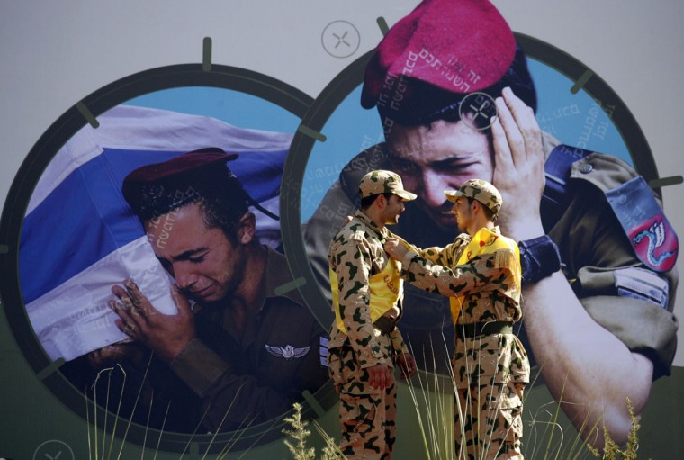 Images of grieving Israeli soldiers adorn a wall as members of the Shiite Muslim Hezbollah movement adjust their sashes during a gathering to listen to a speech by Hezbollah's leader Hasan Nasrallah, delivered via video-link, in the southern Lebanese village of Aita al-Shaab, on the border with Israel on August 16, 2013. The speech commemorated the seventh anniversary of the 2006 July-August war between Lebanon and Israel. Nasrallah accused radical Islamists of responsibility for a car bomb that killed at least 22 people in a Beirut stronghold of his pro-Syria Shiite group. (Mahmoud Zayyat/AFP/Getty Images)