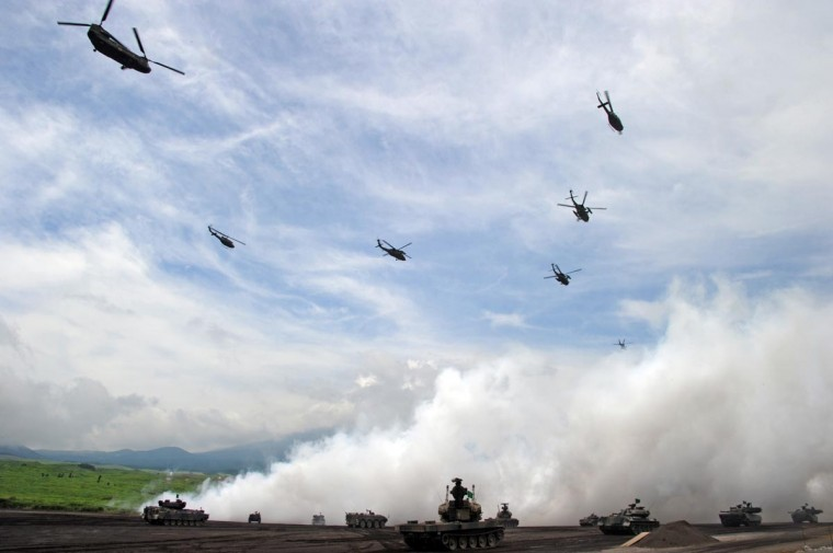 Japanese Ground Self-Defense Forces helicopters fly over armored vehicles during an annual live fire exercise at the Higashi-Fuji firing range in Gotemba, at the foot of Mt. Fuji in Shizuoka prefecture on August 20, 2013. The annual drill involves some 2,400 personnel, 80 tanks and armored vehicles and 30 aircraft and helicopters. (Toshifumi Kitamura/AFP/Getty Images)