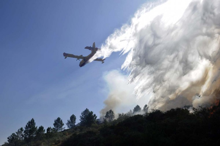 A canadair, an amphibious aircraft purpose-built as a water bomber, drops its load over a wildfire in Penoita in central Portugal. (Francisco Leong / AFP/Getty Images)