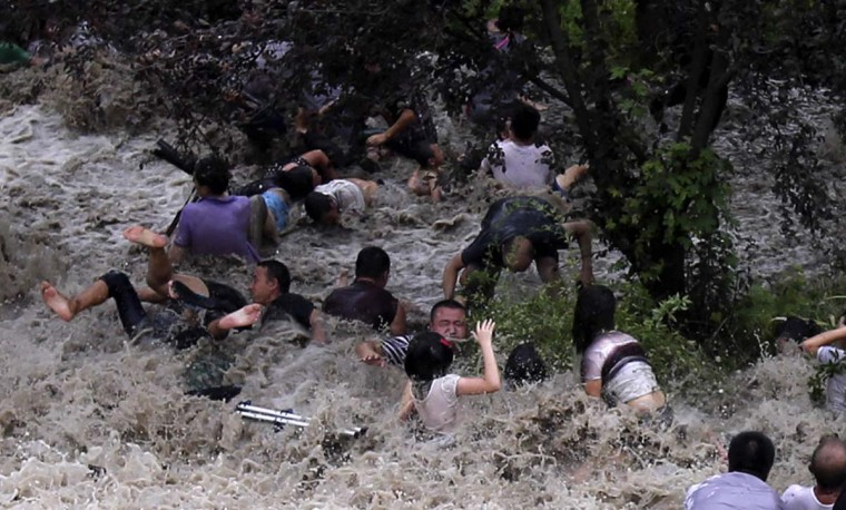 """People are washed away from huge waves from the """"Haining tide"""" -- a daily occurrence when the river tides hit the banks in eastern China's Zhejiang province. The waves surged higher than usual because of Typhoon Trami in the region in Haining. The tides there have attracted spectators for the past two millennia, and it is the scene of an annual Tide-Watching Festival in late summer. (AFP/Getty Images)"""